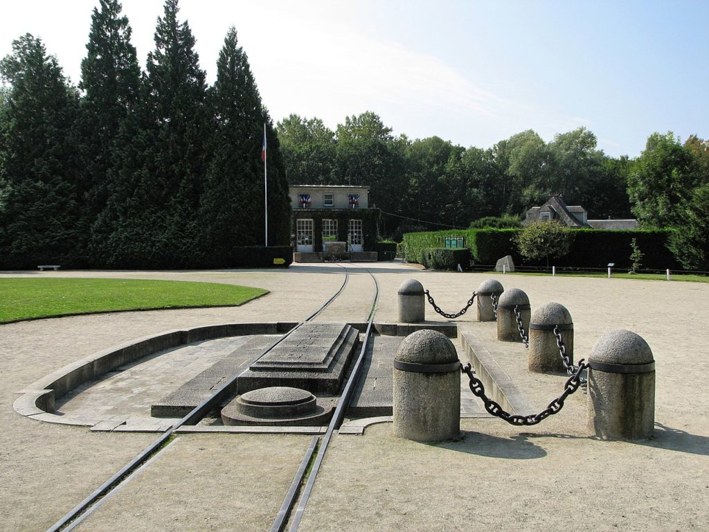 Monument of the Compiègne Wagon, the place where the armistice of Germany was signed, marking the end of WWI. The picture shows rails and the concrete shrine marking the place of the wagon. (CC-BY-SA MagentaGreen via Wikimedia)