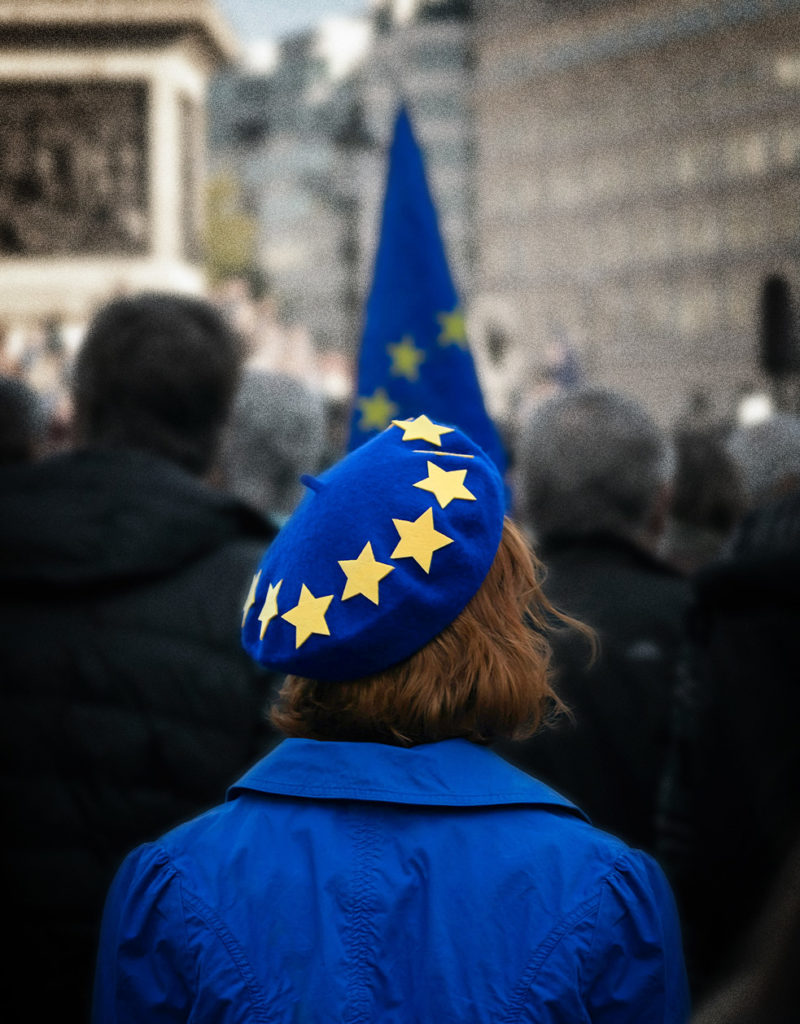 Frau mit Europamütze und blauem Mantel bei Demo